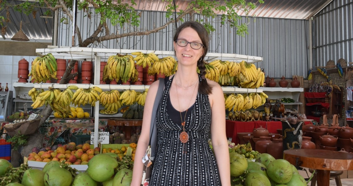 Woman standing in front of fruit stand