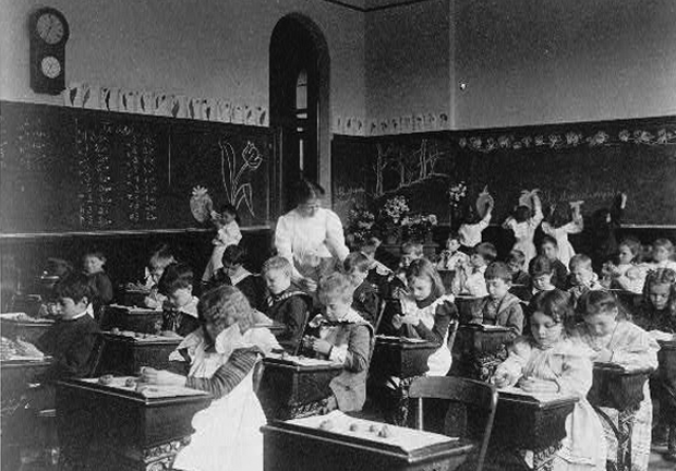 Old grayscale picture of classroom with teacher and students